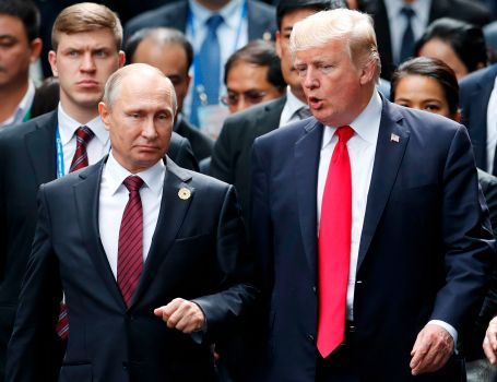"""(FILES) In this file photo taken on November 11, 2017 US President Donald Trump (R) and Russian President Vladimir Putin talk as they make their way to take the """"family photo"""" during the Asia-Pacific Economic Cooperation (APEC) leaders' summit in the central Vietnamese city of Danang. The White House fumed on March 21, 2018, about an embarrassing leak of Trump's decision to congratulate Vladimir Putin on his re-election, with one official describing the disclosure as illegal. A hunt is underway to find the person who leaked Trump's prepared notes for the call, which included a warning """"DO NOT CONGRATULATE,"""" which he ignored.  / AFP PHOTO / POOL / JORGE SILVAJORGE SILVA/AFP/Getty Images"""
